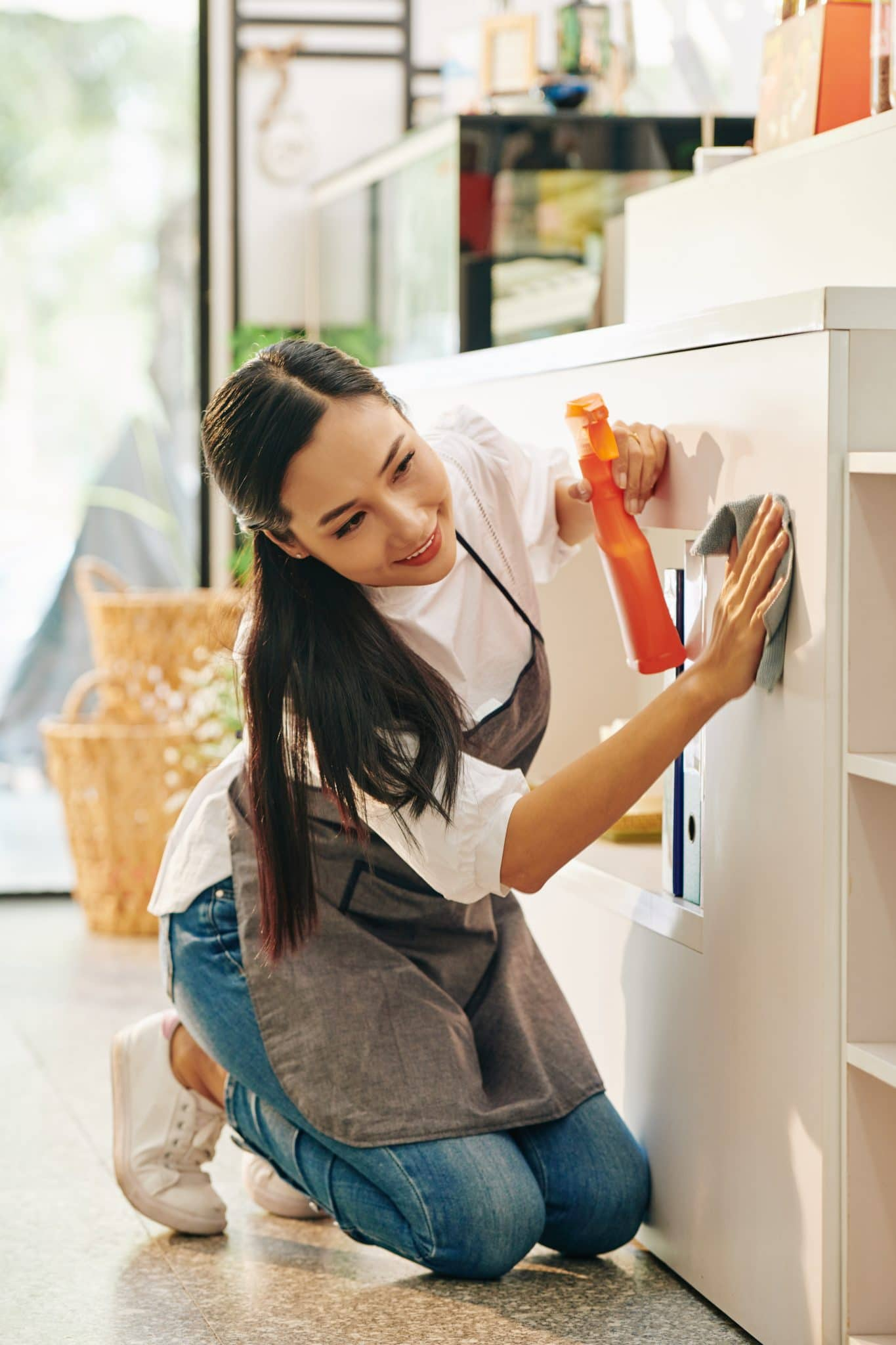 woman-on-her-knees-cleaning-appliances - hazards of bleach on unprotected skin