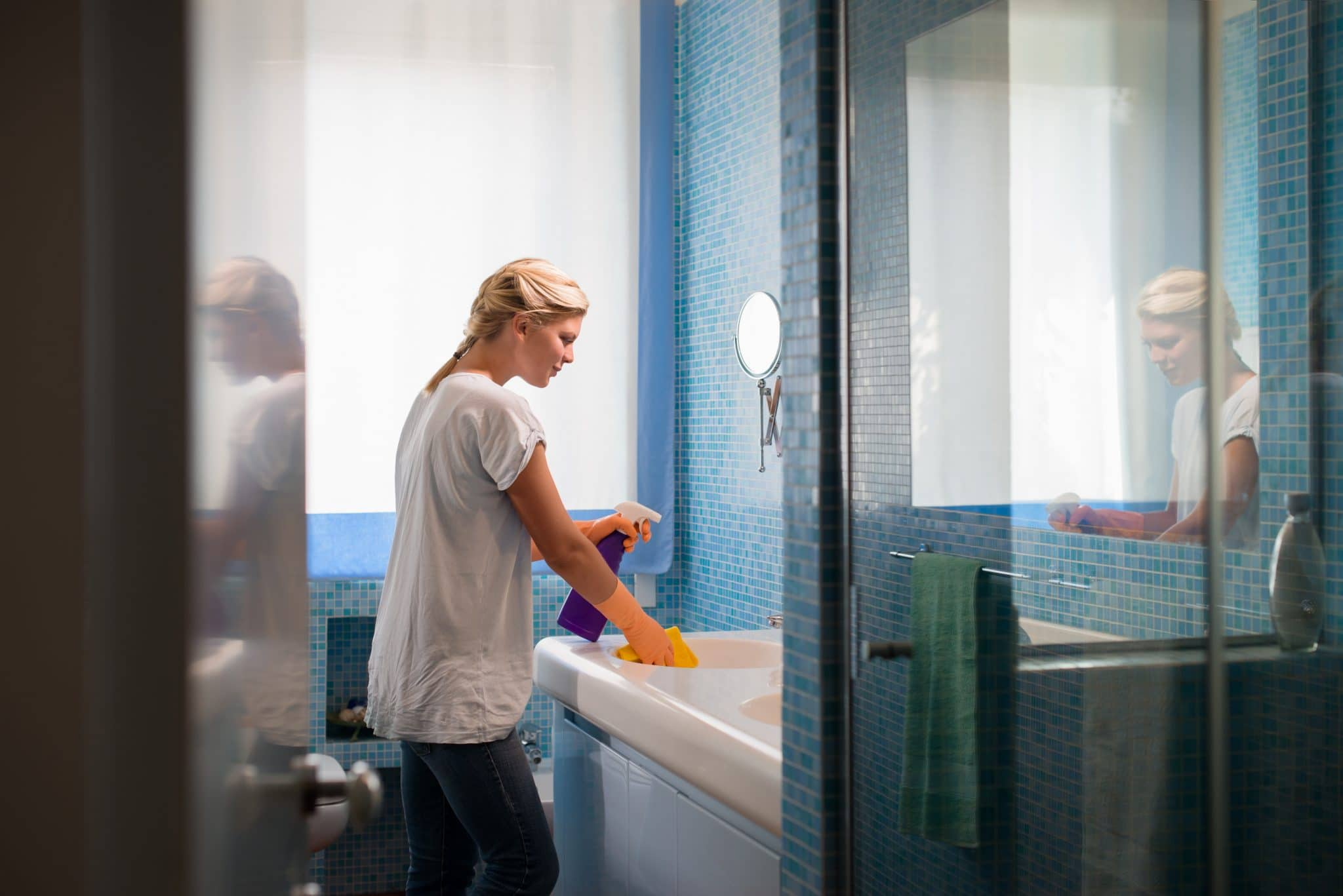 blond-young-woman-cleaning-blue-tiled-bathroom-household-chores-coronavirus-cleaning