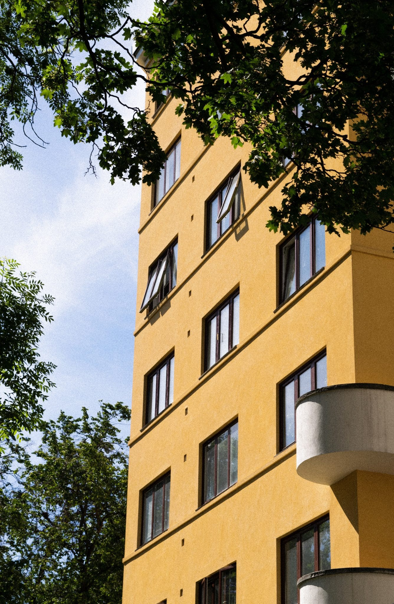 apartment-windows-open-on-the-side-of-a-yellow-brick-building