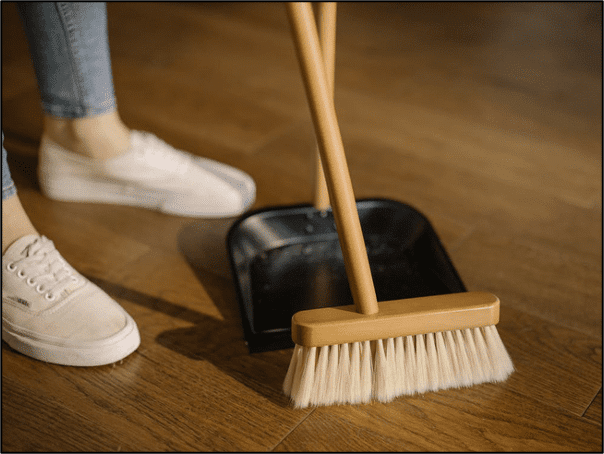 long-handled-broom-and-dustpan-at-womans-feet-in-white-sneakers